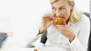 120314064842-woman-emotional-eating-muffin-desk-stress-story-top